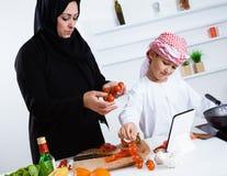阿拉伯孩子在有他的母亲的厨房里 库存图片