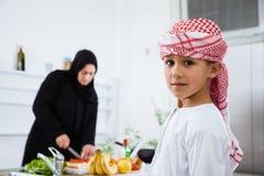 阿拉伯孩子在有他的母亲的厨房里 库存照片