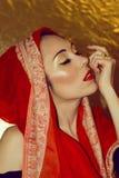 阿拉伯少妇。金子构成。红色衣裳。 免版税库存图片