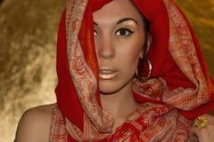 阿拉伯少妇。金子构成。红色衣裳。 免版税库存照片