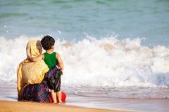 阿拉伯拥抱对海的母亲和儿子 免版税库存照片