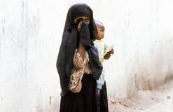 阿拉伯未知的母亲怀有她的一套概括服装的婴儿 库存照片