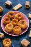 阿拉伯甜点 在蓝色背景的各种各样的东方甜点 果仁蜜酥饼, halva,果汁牛奶冻,芝麻 免版税库存照片