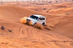 阿拉伯联合酋长国,富查伊拉2017年 19 11在吉普SUVs的越野徒步旅行队在阿拉伯橙红沙子在日落太阳离开 免版税库存图片