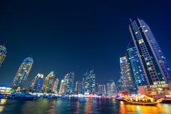 阿拉伯联合酋长国,迪拜- 2013年11月, 30日:迪拜小游艇船坞地平线 迪拜海滨广场海运摩天大楼视图 被停泊的晚上端口船视图 库存图片