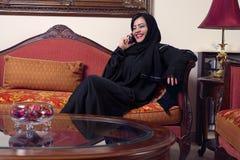 阿拉伯hijab夫人移动电话联系的佩带 免版税库存图片