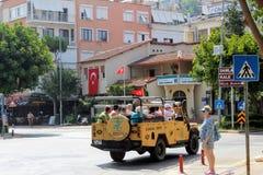 阿拉尼亚,土耳其, 2017年7月:4WD吉普游览的游人乘坐在城市街道下 图库摄影