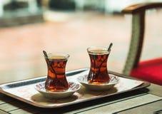 阿拉尼亚,土耳其-, 22 :在传统郁金香玻璃的土耳其茶在Simitci Dunyasi街道咖啡馆的桌上 免版税库存图片