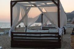 阿拉尼亚-在晚上风景的有四根帐杆的卧床床在帕特拉beac 库存图片