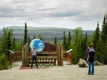 阿拉斯加,美国- 2009年5月29日:北极圈标志和游人 免版税库存照片
