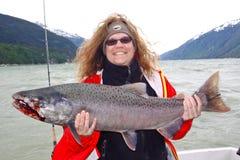 阿拉斯加-拿着大三文鱼的愉快的妇女 免版税库存照片