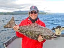 阿拉斯加-拿着大比目鱼的愉快的微笑的妇女 库存照片