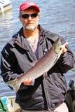 阿拉斯加-有五颜六色的红鲑鱼的人 免版税库存图片