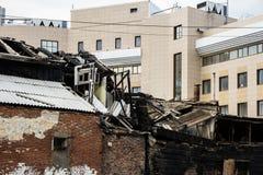 阿斯特拉罕,俄罗斯, 21 2018年3月:在现代办公室前面的被烧焦的老大厦 图库摄影