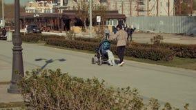 阿斯特拉罕,俄罗斯- 24 2018年4月:走沿伏尔加河堤防的母亲和小孩在晴天 影视素材