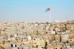 阿曼与大约旦旗子和旗杆的市视图 免版税图库摄影