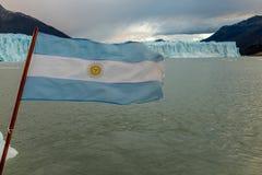 阿根廷旗子振翼在一条小船的后面在佩里托莫雷诺冰川前面的在阿根廷 库存照片