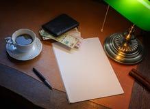 阿根廷金钱,在一张时髦的书桌上的比索点燃与一盏开户的灯 免版税库存照片