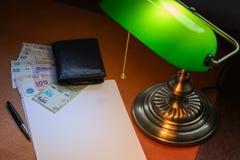 阿根廷金钱,比索,在一张时髦的书桌上点燃与一盏开户的灯 免版税库存照片