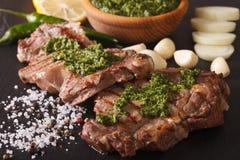 阿根廷烹调:与chimichurri调味汁橡皮防水布的烤牛排 免版税库存照片