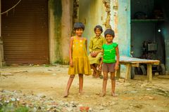 阿格拉,印度- 2017年9月20日:画象两弄脏了美丽的女孩,当男孩微笑后边,佩带黄色 免版税库存照片