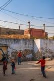阿格拉,印度- 2012年12月:打羽毛球的泰姬陵篱芭和孩子在世界的这奇迹附近 其中一多数 库存照片