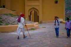 阿梅尔,印度- 2017年9月19日:佩带白色的未认出的老人在穿衣和一条红色头巾,走扔石头 图库摄影