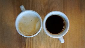阿梅里卡诺咖啡在两个杯子中有木背景 免版税库存照片