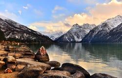阿玛尼向雕刻与雪山和湖扔石头 库存图片