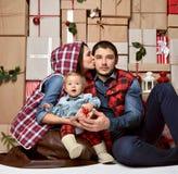 阿皮做父母拥抱在家亲吻庆祝新年的孩子 免版税库存图片