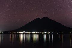 阿蒂特兰湖在危地马拉 长的曝光夜照片写真 火山在背景中 在天空的摇摄星 光反射 免版税库存照片