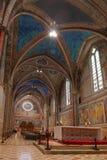 阿西西Basilica Papale di有更低的广场的圣弗朗切斯科圣法兰西斯内部著名大教堂日落的在阿西西,翁布里亚, 图库摄影