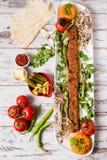 阿达纳Kebab服务与在白色板材的绿色菜 库存照片