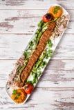 阿达纳Kebab服务与在白色板材的绿色菜 免版税图库摄影