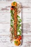 阿达纳Kebab服务与在白色板材的绿色菜 免版税库存图片