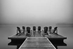 阿迪朗达克在湖船坞的轻便折叠躺椅 免版税库存照片