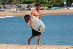 阿鲁加姆湾, 8月08日:拿着他的冲浪板和走在海滩的年轻肌肉冲浪者 库存图片