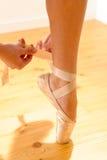 附加她的pointe鞋子的芭蕾舞女演员特写镜头 免版税图库摄影
