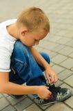 附加鞋带的男孩 图库摄影