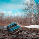 黏附在土和被放弃的汽车在一个晴朗的春日 库存图片