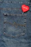 黏附在斜纹布外面的后面口袋的红色心脏 图库摄影