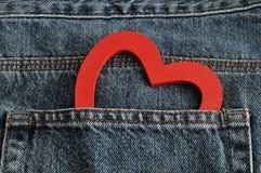 黏附在斜纹布外面的后面口袋的红色心脏 免版税库存照片
