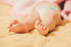 黏附在毯子外面的婴孩的腿 免版税库存图片