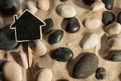 黏附在沙子外面的石头和房子特写镜头在阳光下 库存照片