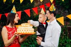 附属的儿童` s生日聚会、食物和甜点 一个年轻家庭庆祝一年儿子 爸爸拿着一个大蛋糕,妈妈是 库存图片