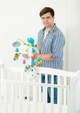 附有在他的婴孩` s轻便小床的人画象玩具转盘 库存图片