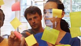 黏附稠粘的笔记的公和女性商业主管在玻璃