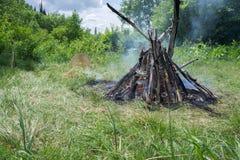 附近灼烧的大篝火和一个shamanic小手鼓,在一块绿色沼地在森林里 库存照片