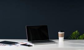 附近片剂计算机,智能手机,纸图表,一杯咖啡 在背景中黑暗的墙壁 免版税库存照片