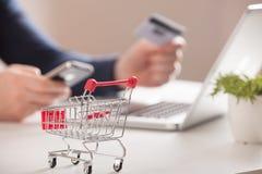 附近银行卡膝上型计算机和微型购物车在白色背景顶视图 免版税图库摄影